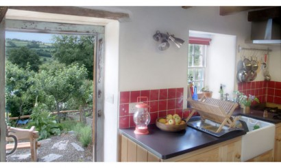 The kitchen and view to the garden. Photo from Under the Thatch